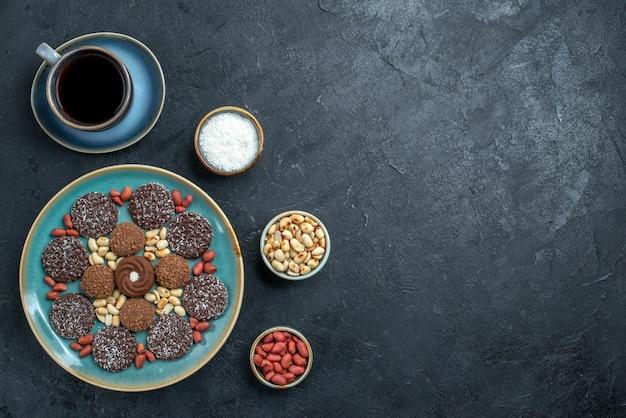 灰色の背景にナッツをベースにしたさまざまなクッキーチョコレートの上面図キャンディーボンボンシュガー甘いケーキクッキー