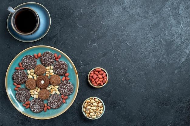 灰色の背景にナッツをベースにしたさまざまなクッキーチョコレートの上面図キャンディーボンボンシュガースイートケーキクッキー