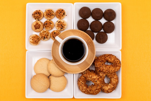 Top view different cookies in square plates and coffee cup on yellow surface