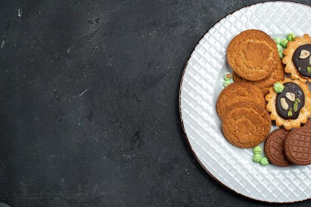 灰色の机の上にあるさまざまなクッキーの甘くておいしいクッキーの上面図