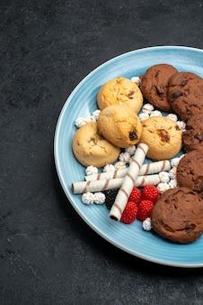 灰色の表面にあるさまざまなクッキーの甘くておいしいクッキーの上面図