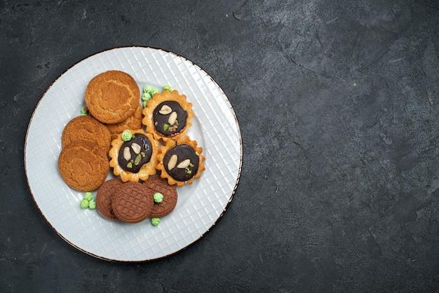 Вид сверху различных печений, сладких и вкусных печений внутри на серой поверхности