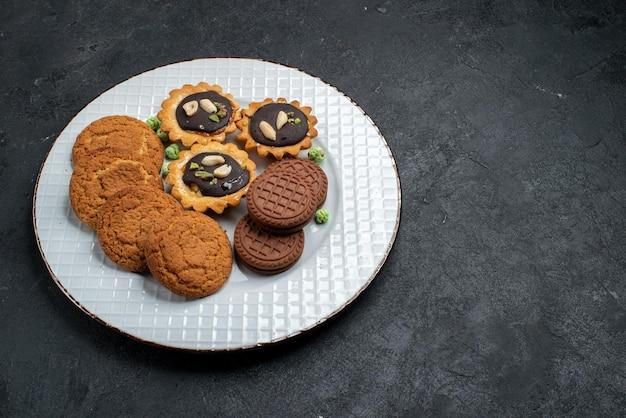 ダークグレーの表面にあるさまざまなクッキーの甘くておいしいクッキーの上面図