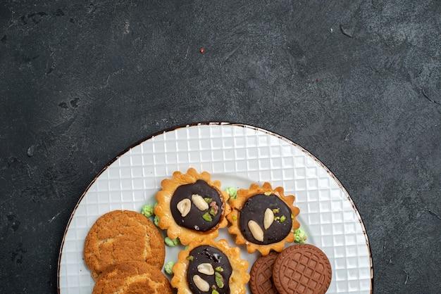 灰色の机の上のさまざまなクッキー甘くておいしいクッキーの上面図