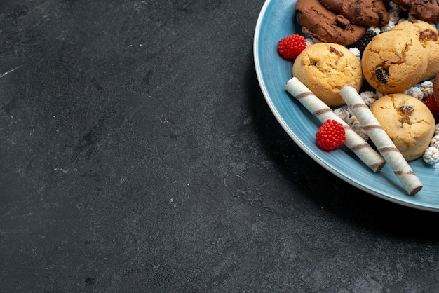 Vista dall'alto diversi biscotti dolci e deliziosi all'interno su una superficie grigio scuro