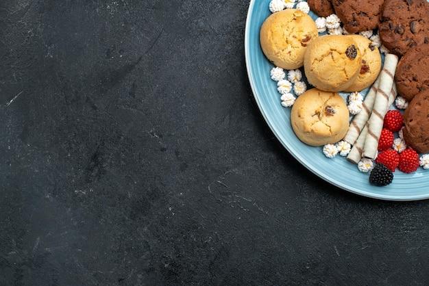 Vista dall'alto diversi biscotti dolci e deliziosi all'interno sulla superficie grigia