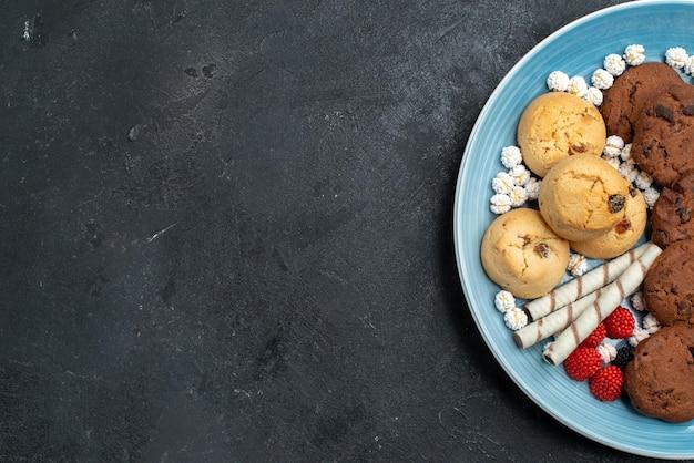 灰色の表面の内側に甘いさまざまなクッキーの上面図