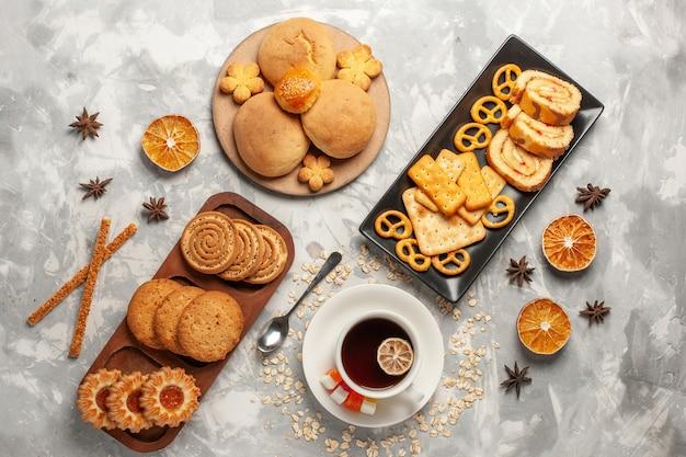 흰색 표면 쿠키 비스킷 설탕 베이킹 케이크 달콤한 파이에 케이크와 차 한잔 상위 뷰 다른 쿠키