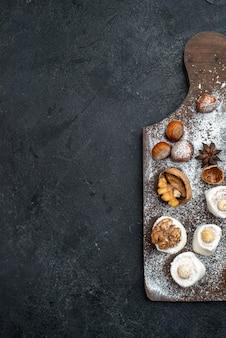 Вид сверху разные печенья с тортами и грецкими орехами на темно-сером столе