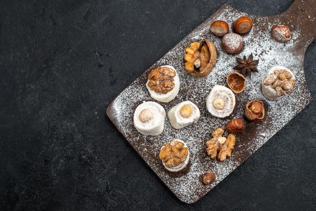 Вид сверху различных печений с тортами и грецкими орехами на темно-серой поверхности