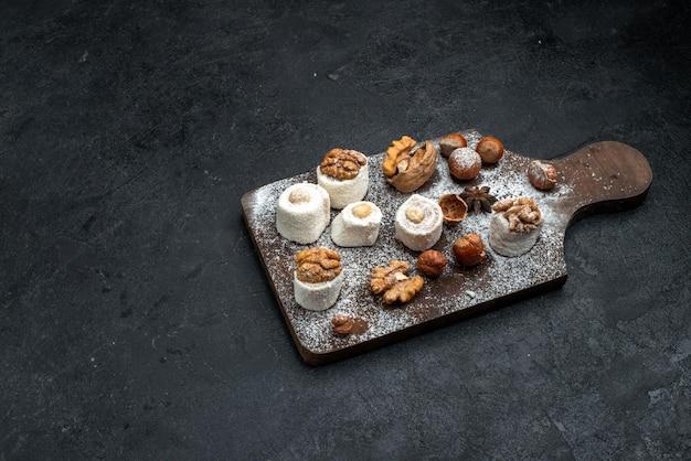 ダークグレーの表面にケーキとクルミが入ったさまざまなクッキーの上面図