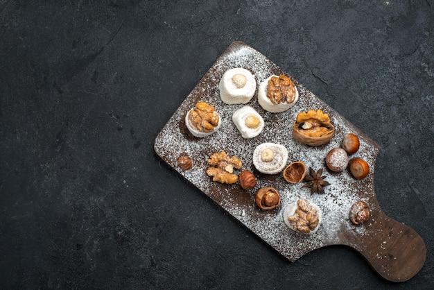 Vista dall'alto diversi biscotti con torte e noci sulla scrivania grigio scuro
