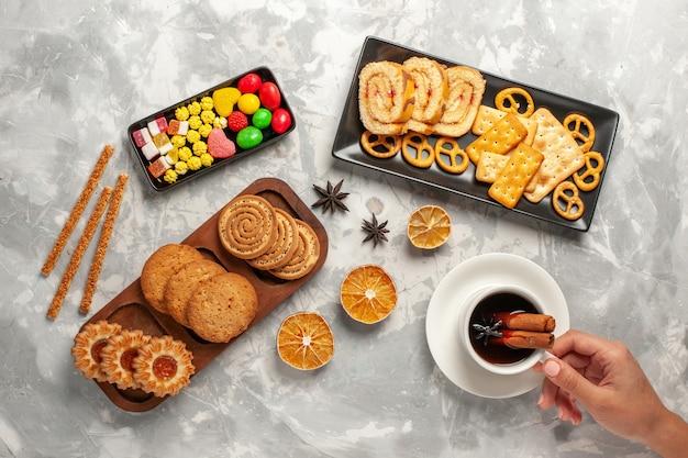 上面図白い机の上のキャンディーとお茶とさまざまなクッキークッキービスケットシュガーベイクケーキ甘いパイ
