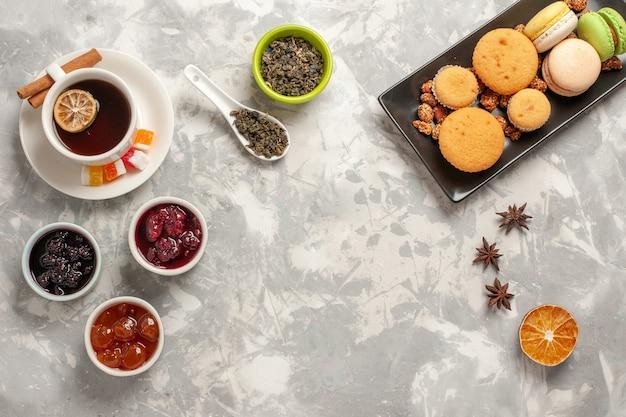 上面図白い背景の上のさまざまなジャムとお茶のさまざまなクッキービスケットシュガーパイケーキ甘いクッキー