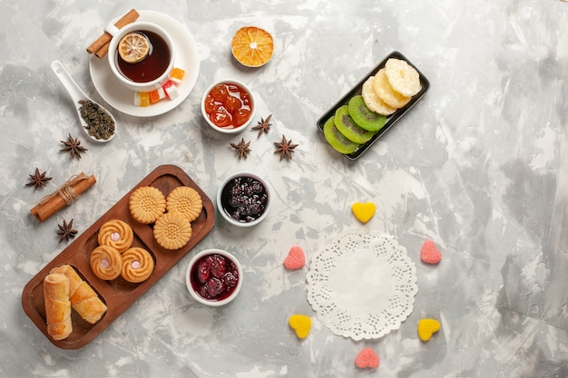 Top view different cookies with dried fruits and cup of tea on light white surface biscuit sugar pie cake sweet cookie