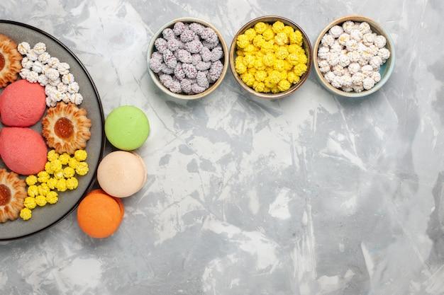 Вид сверху разные печенья с французскими макаронами и конфетами на белом фоне, конфеты, сахар, сладкая выпечка, торт, чайный пирог, печенье