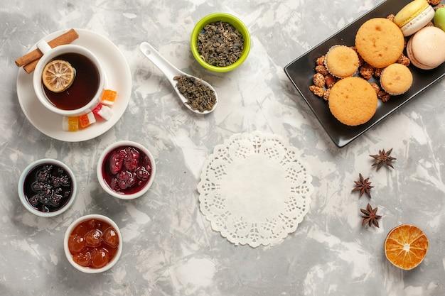 Vista dall'alto diversi biscotti con marmellate e tazza di tè sul biscotto bianco scrivania torta di zucchero torta dolce biscotto