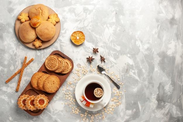 上面図白い背景の上の小さなケーキとお茶のカップとさまざまなクッキークッキービスケットシュガーベイクケーキ甘いパイ