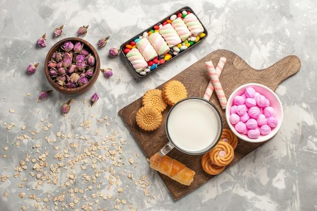 Vista dall'alto diversi biscotti con marshmallow e caramelle sulla superficie bianca zucchero biscotto caramelle torta goodie bonbon sweet
