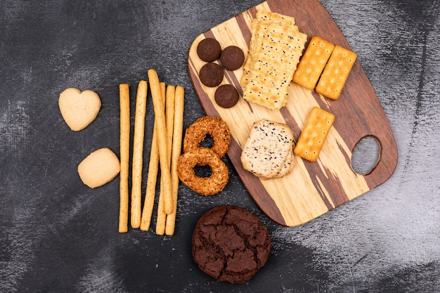 Top view different cookies on wooden board on dark surface