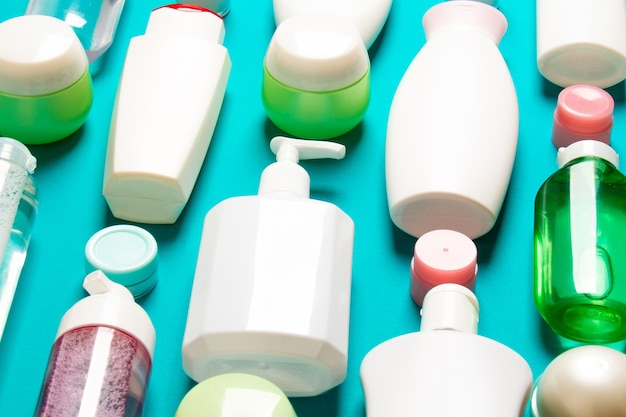 Top view of different cosmetic bottles and container for cosmetics on colored background. flat lay composition with copy space.