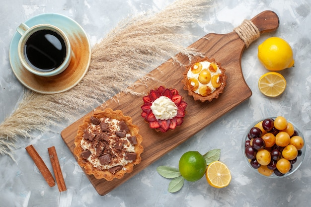 Top view different creamy cakes fruity cakes with lemon cherries tea on white desk cake bake biscuit sweet sugar fruit
