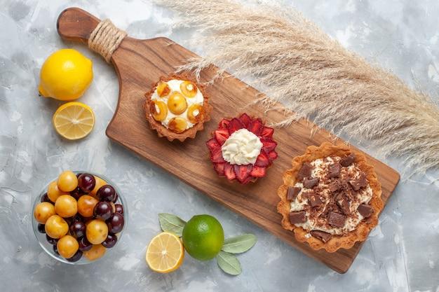 Vista dall'alto diverse torte cremose torte fruttate con limone e ciliegie sulla scrivania bianca torta cuocere biscotti zucchero dolce frutta