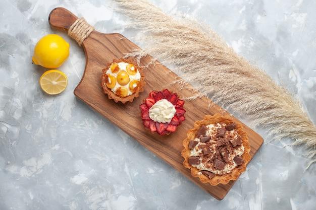 上面図さまざまなクリーミーなケーキフルーティーなケーキとレモンの白い机の上のケーキ焼きビスケット甘い砂糖の果実