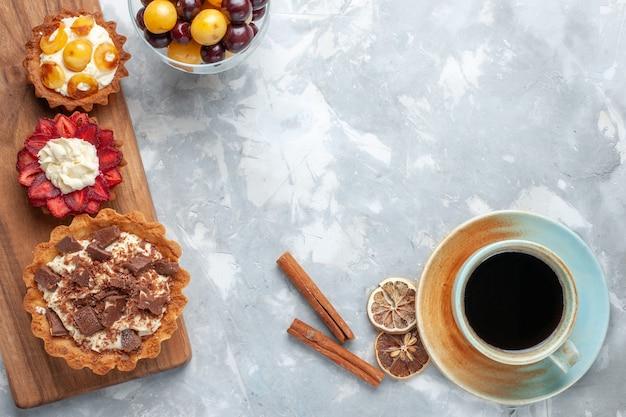 Vista dall'alto diverse torte cremose con ciliegie e tè sulla torta bianca scrivania cuocere biscotti zucchero dolce frutta