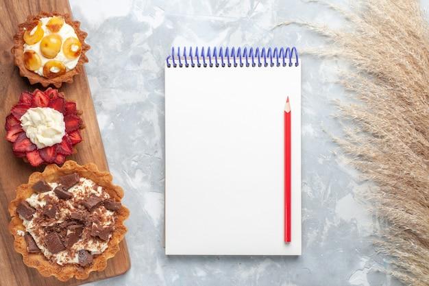 Vista dall'alto diverse torte cremose con cioccolato e frutta blocco note sulla scrivania bianca torta cuocere biscotti zucchero dolce frutta