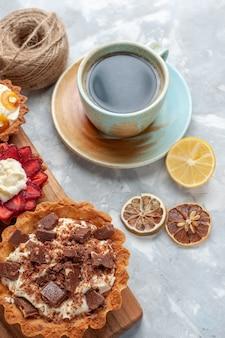 Vista dall'alto diverse torte cremose con cioccolato e frutta tè sulla scrivania bianca torta cuocere biscotti zucchero dolce frutta