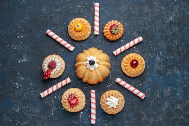 Vista dall'alto di diverse deliziose torte con panna e frutti di bosco insieme a caramelle rosa su torta biscotto scuro, frutti di bosco cuocere dolce