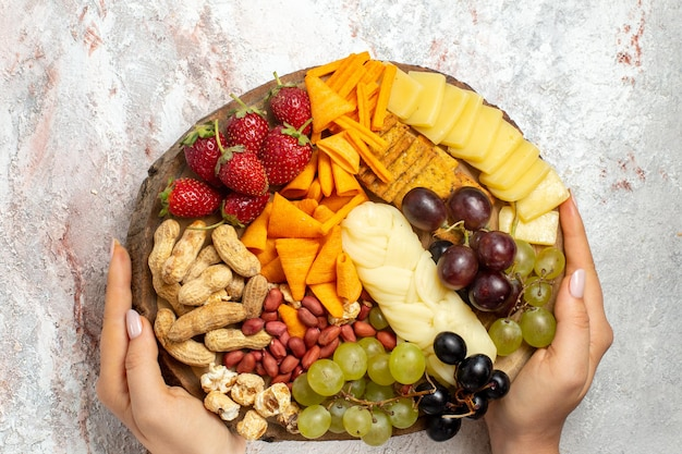 Vista dall'alto di diversi deliziosi spuntini uva fresca cips formaggio e noci sulla superficie bianca