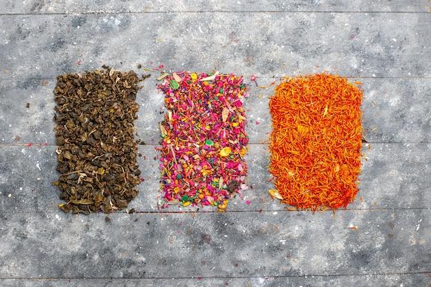 Vista dall'alto diversi condimenti secchi sulla scrivania rustica grigia Foto Gratuite