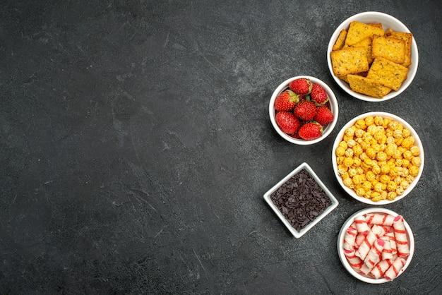 Вид сверху разные крекеры, фрукты и конфеты