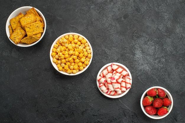 Vista dall'alto diversi cibi patatine frutta e caramelle