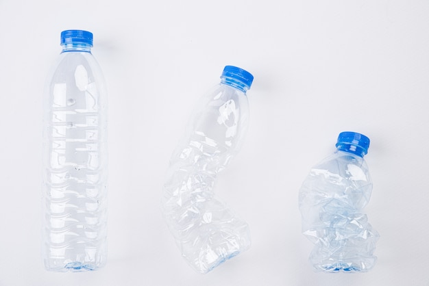 Top view of different empty plastic water bottles from full to crushed on white