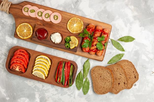上面図さまざまな食品組成トマトレモンソーセージピーマンとパンローフライトホワイトデスクミール野菜フードランチ写真