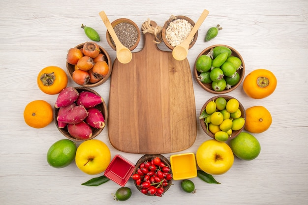 Вид сверху разных свежих фруктов внутри тарелок на белом фоне тропических спелых цветов диеты сочные экзотические здоровый образ жизни