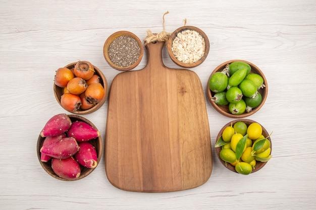 Вид сверху различных свежих фруктов внутри тарелок на белом фоне тропических спелых экзотических здоровых цветов диеты