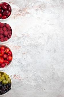 平面図ライトホワイトの背景にプレート内のさまざまな新鮮な果物ベリーフルーツ野生植物の木新鮮