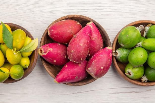 Вид сверху различных свежих фруктов внутри тарелок на белом фоне экзотических тропических спелых диет цвета здорового образа жизни