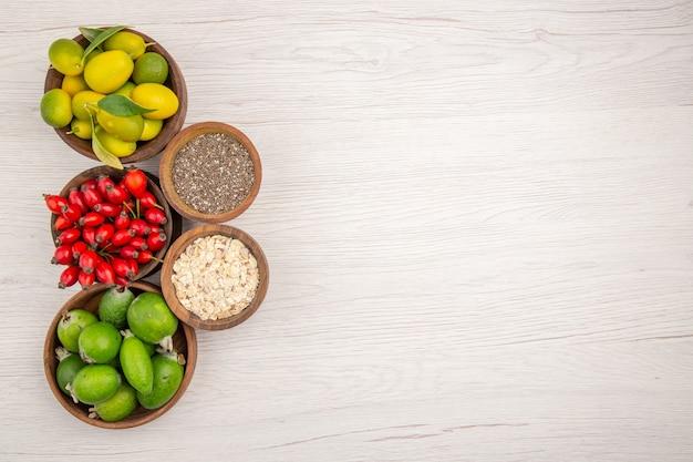 Вид сверху разные свежие фрукты внутри тарелок на белом фоне экзотическая спелая диета здоровый образ жизни тропический цвет свободное пространство