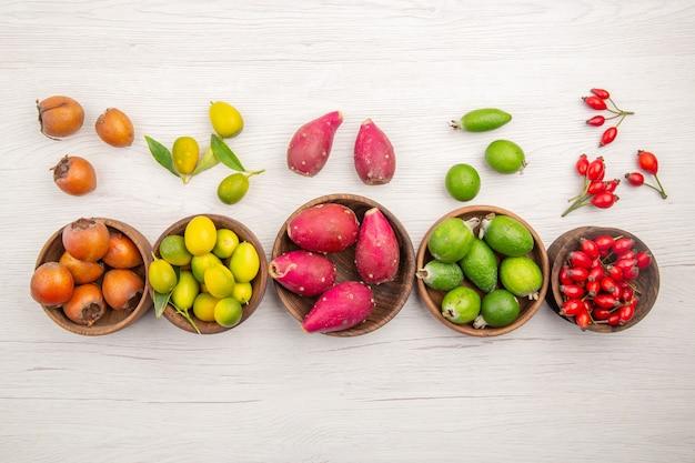 Вид сверху различных свежих фруктов внутри тарелок на белом фоне экзотических тропических спелых диет здорового образа жизни