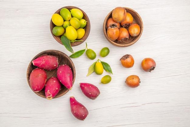 Вид сверху различных свежих фруктов внутри тарелок на белом фоне фруктов тропической спелой диеты экзотического цвета