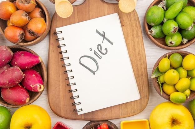 Вид сверху различных свежих фруктов внутри тарелок на белом фоне тропических спелых цветов диета экзотических здоровый образ жизни мягкий