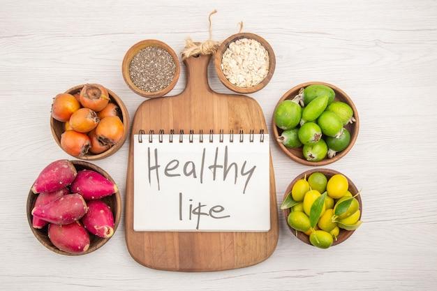 Вид сверху различных свежих фруктов внутри тарелок на белом фоне тропических спелых здоровых цветов диеты