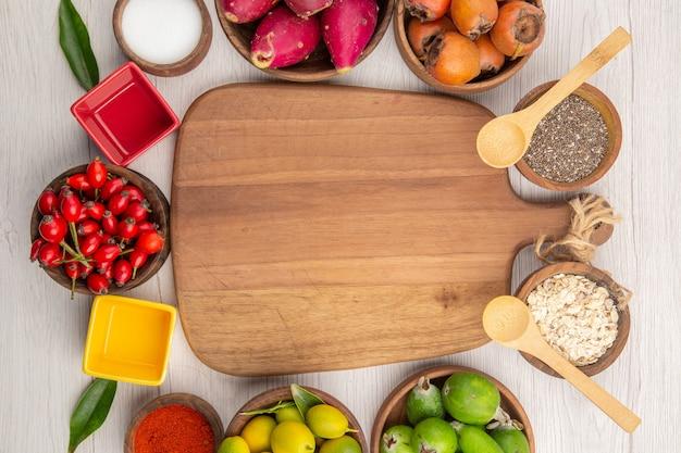 Вид сверху различных свежих фруктов внутри тарелок на белом фоне тропических спелых экзотических диеты для здорового образа жизни