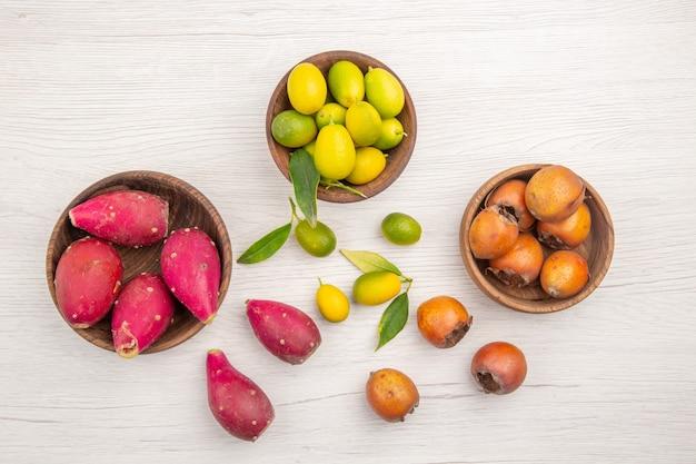 上面図白い机の上のプレート内のさまざまな新鮮な果物トロピカル熟したダイエットエキゾチックな色