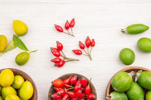 Вид сверху разных свежих фруктов внутри тарелок на белом полу, экзотическая спелая диета, цвет здорового образа жизни, тропический